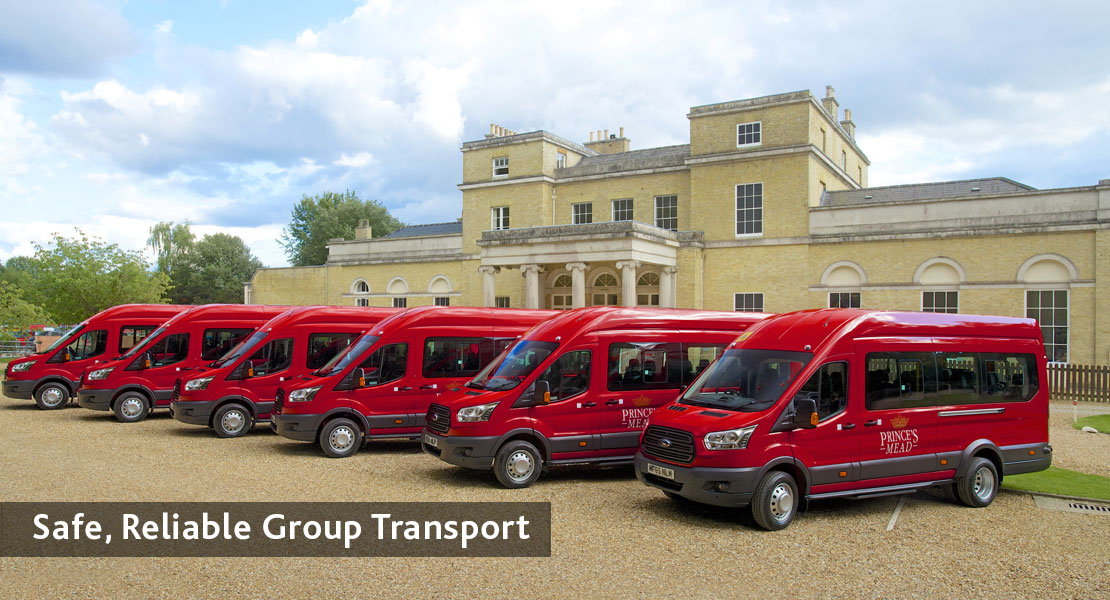 A row of six red school minibuses lined up in parallel outside a school building