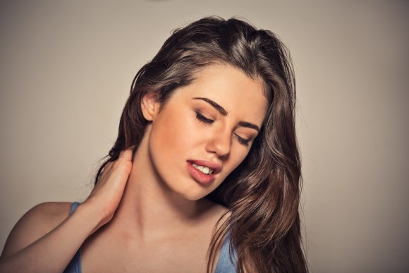 Back and spine disease. Closeup portrait tired woman massaging her painful neck isolated on gray wall background. Human face expression. Chronic fatigue disease