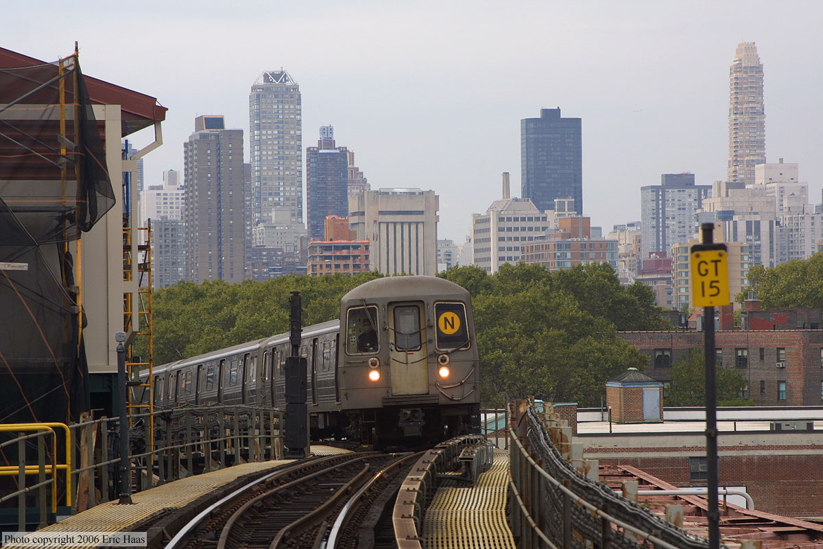 Astoria bound N train makes the classic approach to Queensboro Plaza, view of Manhattan skyline behind