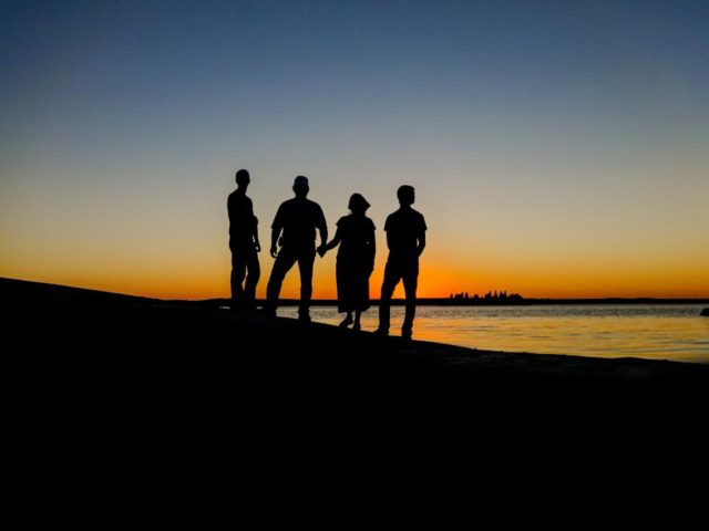 four-silhouettes-watching-sunset-together