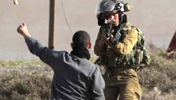 Israeli soldier points gun at child