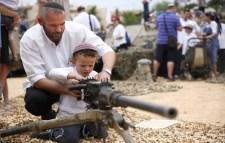 Israeli man shows his son how to fire a machine gun