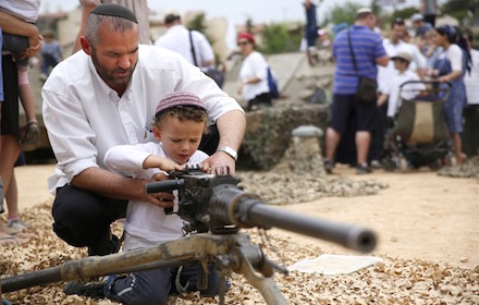 Israeli man shows his son how to fire a machine gun