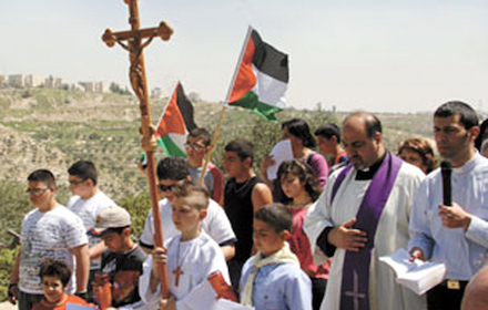 Palestinian Christians holding a cross and a Palestinian flag