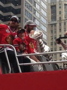 Duncan Keith with his son and Brent Seabrook holding the Stanley Cup.