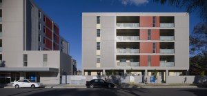Instead of a series of small domestic windows in the facade, Redshift's Yagoona apartments consolidate many smaller windows and doors into the large scale expression of the recessed balconies that look over the street.