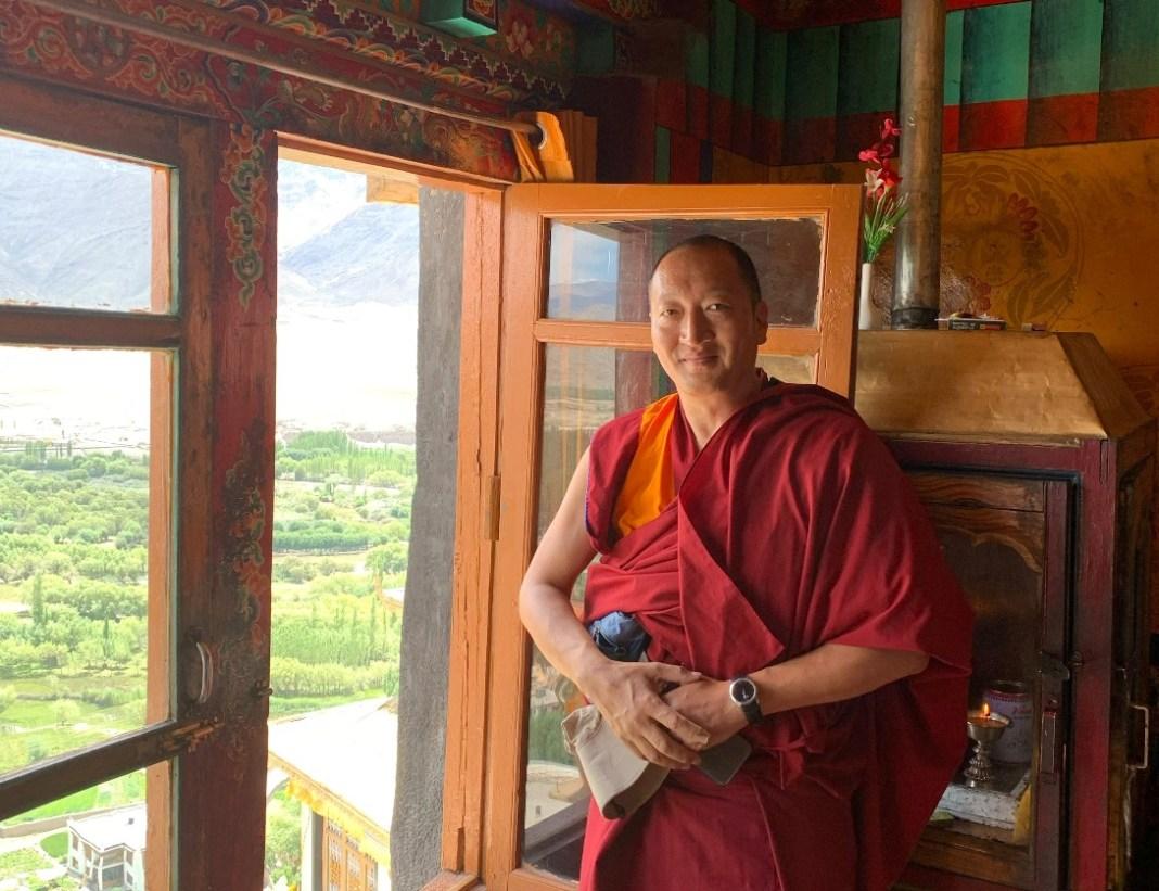 tibetischer-mönch-steht-vor-geöffnetem-fenster