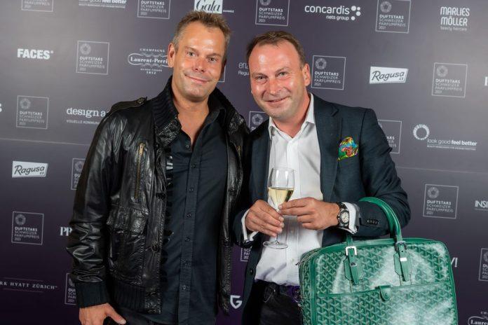 zwei-männer-vor-fotowand-mit-handtasche-und-sekt-in-der-hand