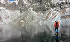 Hikers on the crystal clear surface of the frozen Velke Hincovo Pleso lake