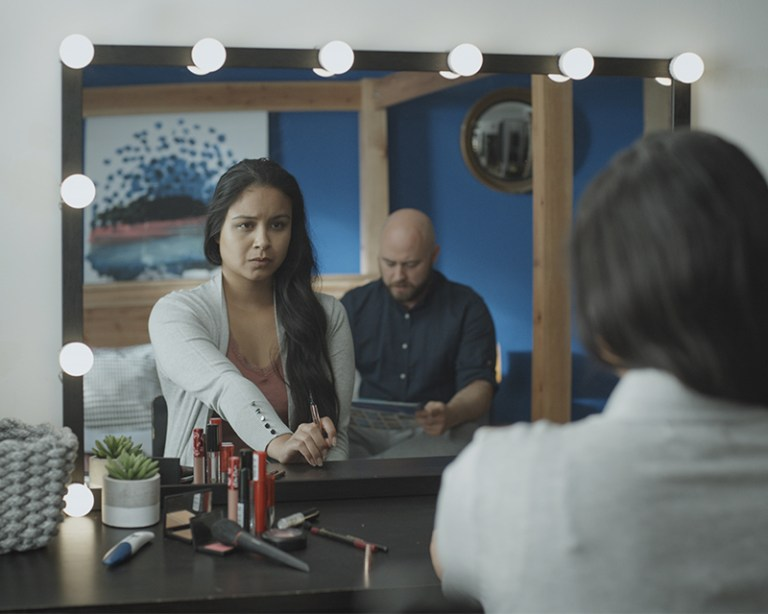 Woman looking nervously into mirror