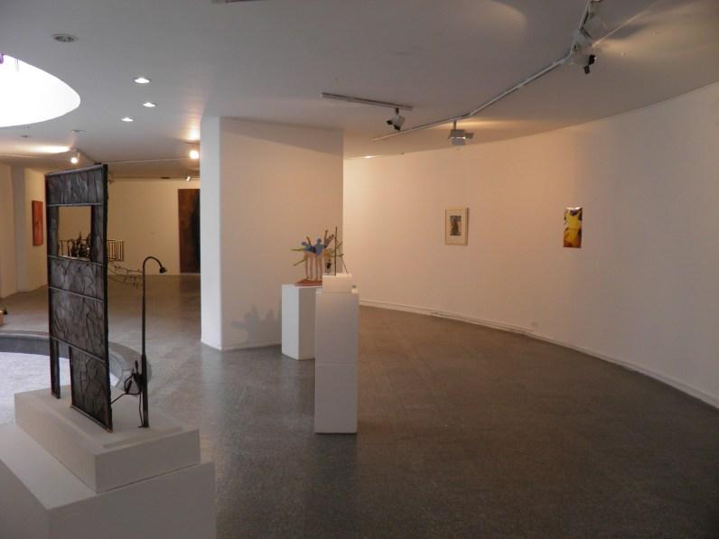Salón de Nuevas Expresiones Plásticas. Vista general Piso 1. Derecha: Ricardo Villegas, Bogotá (1981); centro al fondo: Susana Camaró, Bailarinas (S.F.);izquierda al fondo: registro fotográfico de la obra de Clarita Fierro, Aérea #2 (1981).