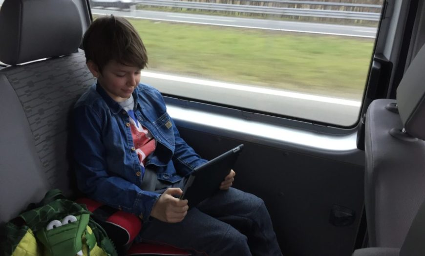 child holding a tablet onboard a VW van
