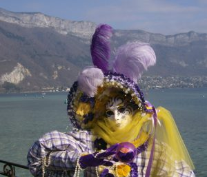 lady wearing carnival clothes and mask by lake Annecy