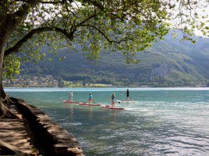 Four children on stand up paddles on lake Annecy