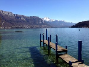 dock with birds sitting on it by lake Annecy