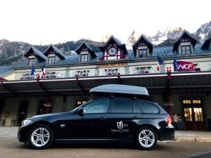 black BMW with a roof box in front of Chamonix train station