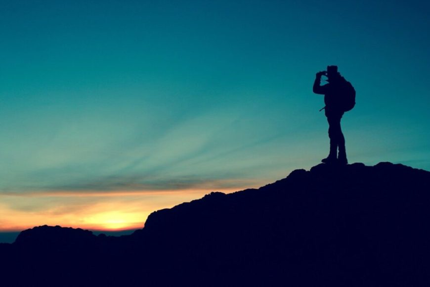 Hiker with binoculars on the top of the mountain