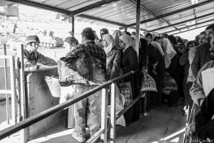Israeli soldier and Palestinians at Huwara checkpoint in Nablus