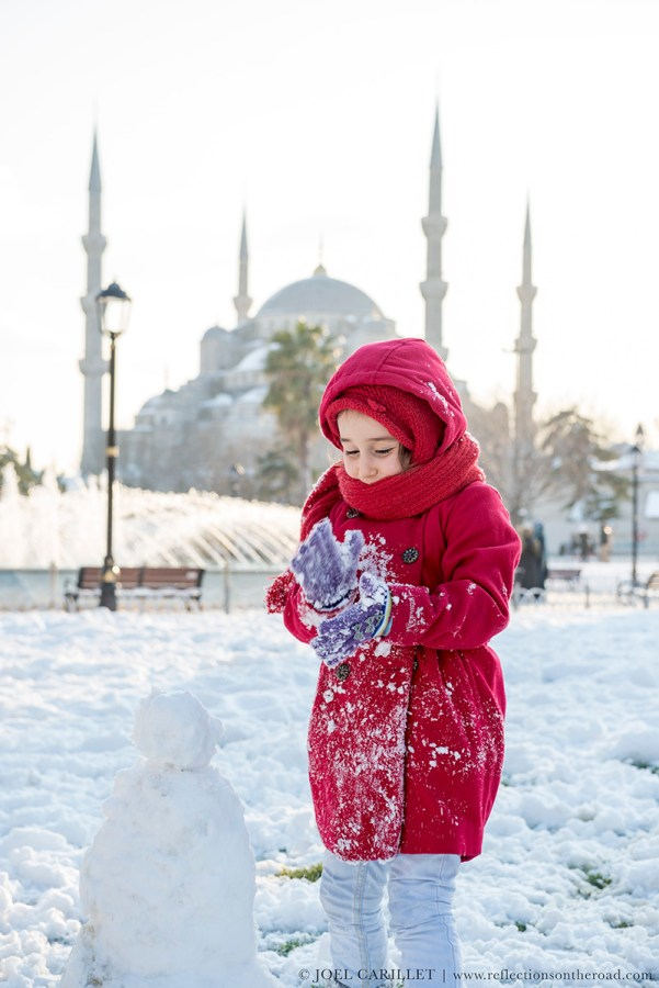 Girl building snowman in Istanbul, Turkey