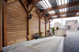 スロープ横には目隠しのフェンス、カーポートの屋根は明かりが入ります