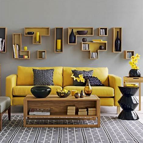 Un sofá amarillo en un salón decorado en gris.