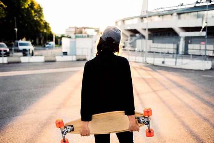 Ung kvinna med keps och skateboard