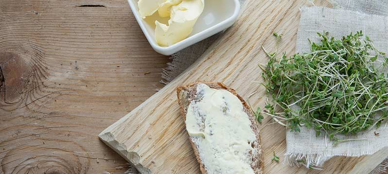 Photographie d'une tranche de pain beurrée, d'une motte de beurre et d'une poignée de cresson