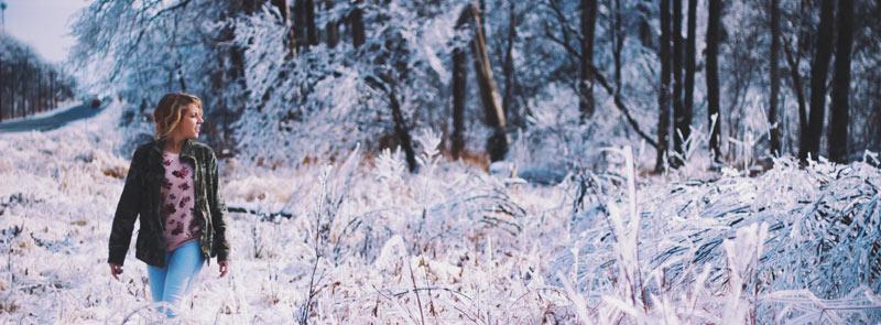 Photographie d'une femme se promenant en pleine nature en hiver, sous la neige