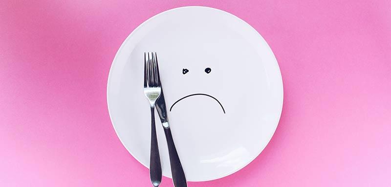 Photographie d'une assiette blanche vide avec un smiley triste et une paire de couverts sur un fond rose afin d'illustrer les dangers du jeûne et des régimes amaigrissants restrictifs pour perdre du poids.