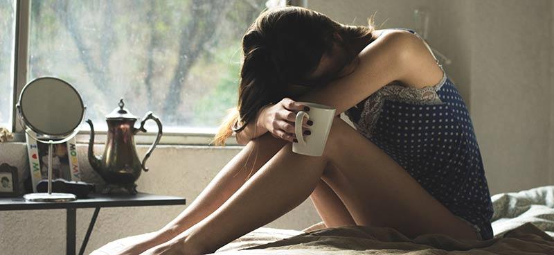 Photographie d'une femme triste, la tête entre ses mains, assise sur son lit avec une tasse de thé à la main car elle n'arrive pas à perdre du poids