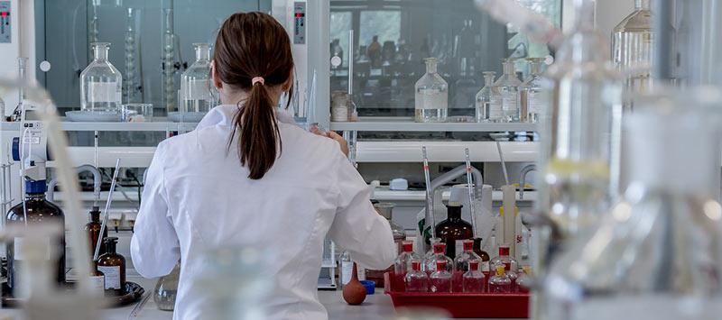 Scientifique prise en photo de dos, en train d'analyser des échantillons dans un laboratoire d'analyse