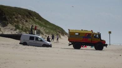 Photo of Kitesurfer met auto vast in het zand