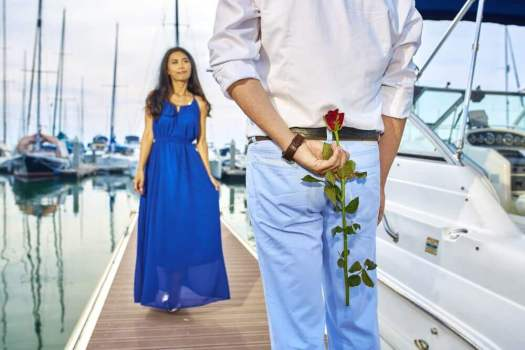 a man with a rose behind his back and a woman approaching him