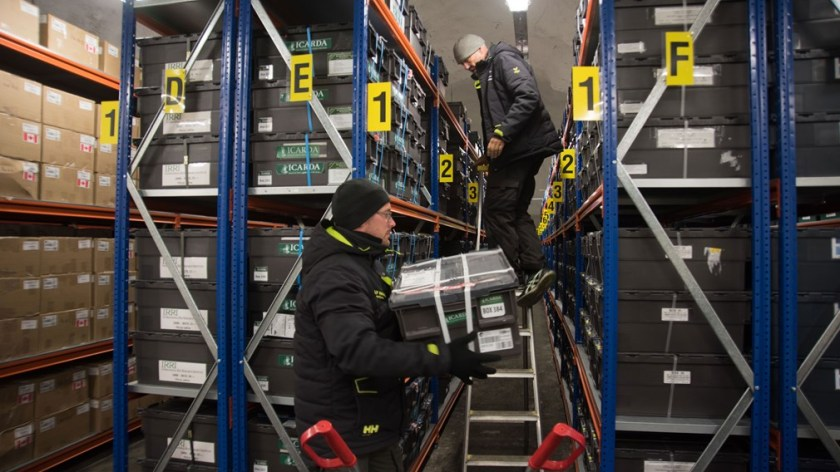 NordGen staff, Fredrik Kollberg (left) and Åsmund Asdal bring new seed boxes in to final position in the Vault shelves