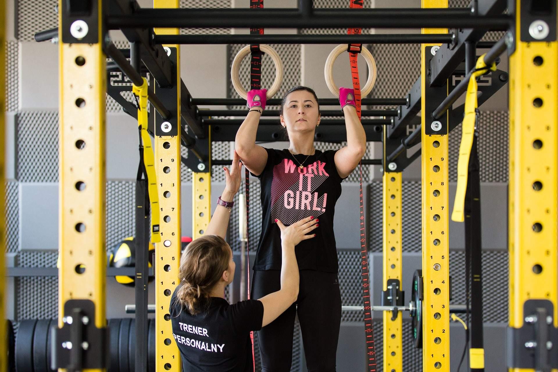 Nasza trenerka osobista wykorzystuje kółka gimnastyczne do urozmaicenia treningu w studiu treningu personalnego RehaFit.