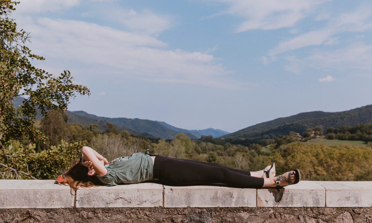 A person lies down on a short wall in front of an open, green vista.