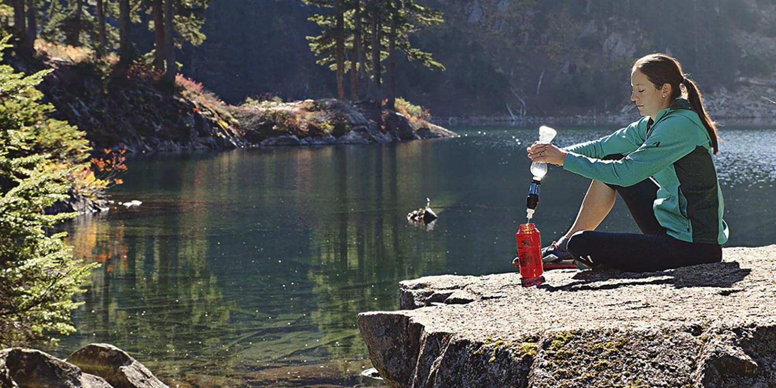 Seorang pejalan kaki mengisi ulang botol airnya dari danau menggunakan penyaring pemerasan