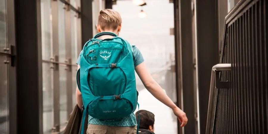 seorang pengelana yang menaiki tangga di stasiun dengan tas ransel perjalanan mereka di