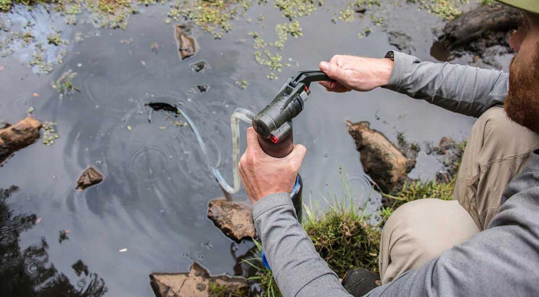 Seorang pejalan kaki mengisi ulang botol airnya dari sungai dengan menggunakan filter pompa