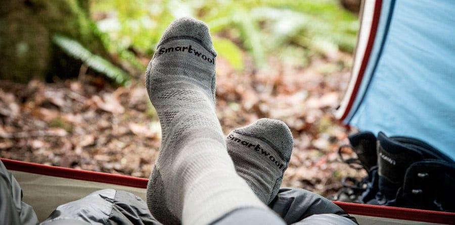 kaus kaki di kaki backpacker melihat keluar dari dalam tenda