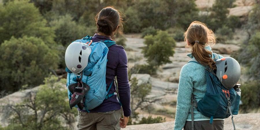 dua pendaki dengan perlengkapan panjat terpasang pada tas punggung pendakian mereka