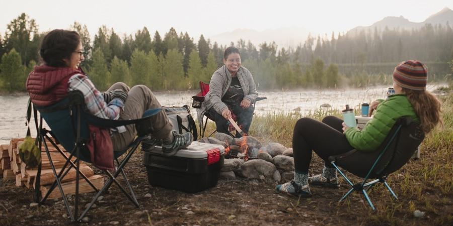 Tiga wanita duduk mengelilingi api unggun di kursi kamp