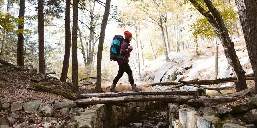 Seorang backpacker berjalan melintasi jembatan penyeberangan di hutan