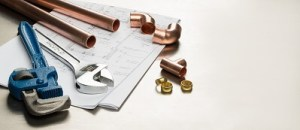 Copper pipes, fittings, and tools on papers