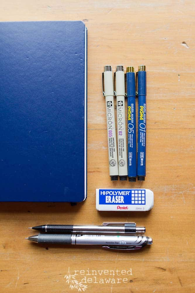 blue bullet journal and various pens