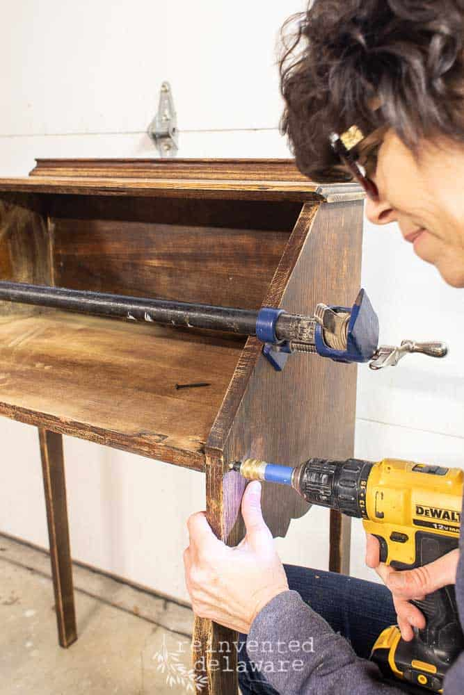 lady repair fold down desk using power drill with countersink drill bit and clamp
