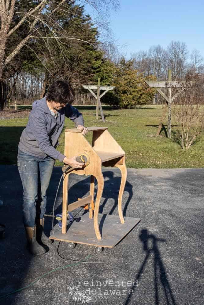 lady sanding antique oak fold down desk with DeWalt sander