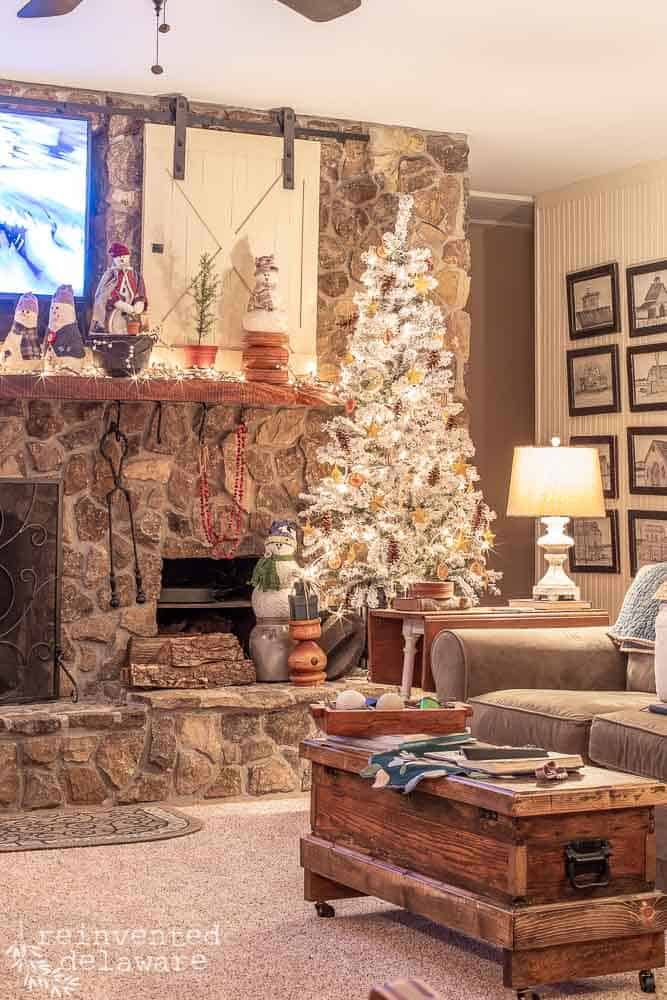 living room, mantle with snowmen and Christmas tree decorated with handmade ornaments