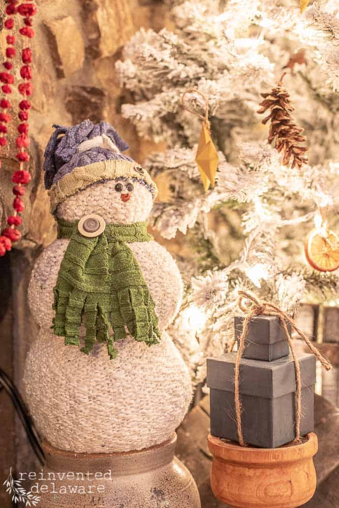 close up of handmade snowman with painted gift boxes near and Christmas tree in background