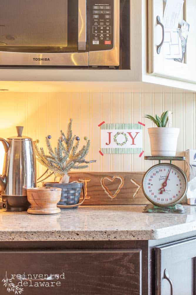 """cage area on kitchen counter showing percalator, small Chrismas tree and """"Joy"""" wall art"""